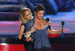 One of the many not-at-all-scripted moments at the 2014 MTV Movie Awards Rita Ora rips the shirt of Best Shirtless Performance Winner Zac Efron