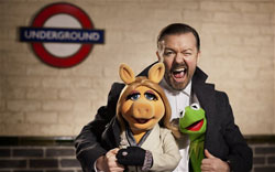 Ricky Gervais gets cozy with Miss Piggy and Kermit the Frog in the top 2014 family film, Muppets Most Wanted